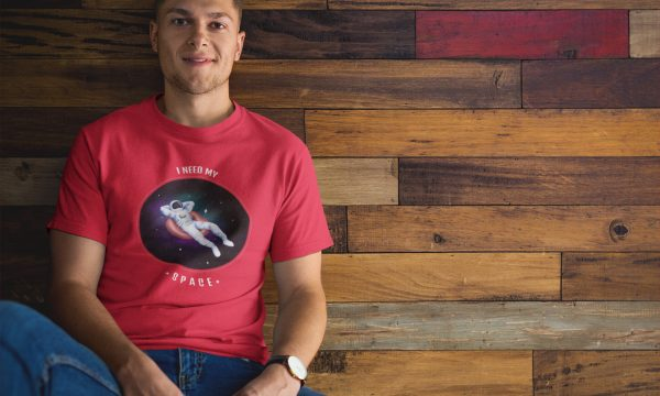 man-wearing-a-tshirt-mockup-while-sitting-against-a-wooden-wall-a17849